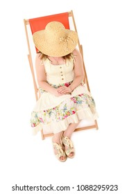 Girl wearing a lemon dress and sunhat, sitting in an orange deck chair and looking downwards. Taken in studio against white background.