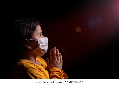 Girl wearing mask for protection against Covid-19 coronavirus pandemic. She is praying God for a cure and help. Copy space.
