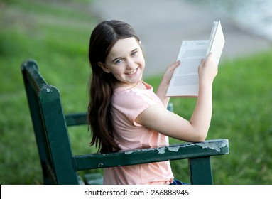 Girl wearing orange shirt outdoors on a park bench reading