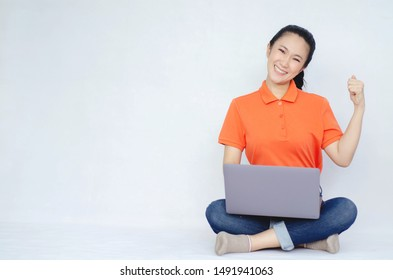 A girl wearing a orange shirt, sitting on the floor and placing a notebook computer on a white background.Women are working With a computer.Women are happy to succeed.Copy Space.Do not focus on object