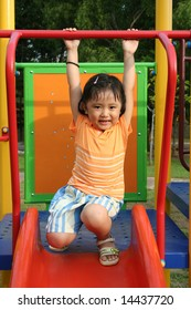 Girl wearing orange tee on the slides in the park