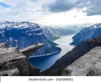 A girl wearing pink jacket stands at the hanging rock formation, Trolltunga with a view on Ringedalsvatnet lake, Norway. Slopes of the mountains are partially covered with snow. Freedom and happiness