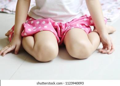 Girl wearing pink skirt siting in W posture on the white floor. W Sitting is when a child is sitting on their bottom with both knees bent and their legs turned out away from their body