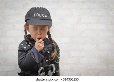 Girl wearing a police costume blowing the whistle