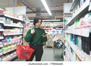 A girl wearing a red basket uses a smartphone at the supermarket when shopping. A woman writes a message in a supermaket. Shopping in a supermarket.