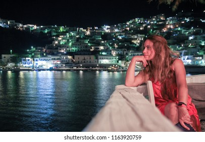 A girl wearing a red dress stares with her hand holding her head towards the Aegean sea, in the island of Astypalaia, Greece, during summer at night time.