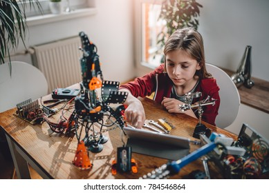 Girl wearing red hoodie building a robot at home and using digital tablet