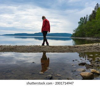 Girl wearing red jacket walking on the beach by a lake in the High Coast area, Northern Sweden. Reflections in the water, cloudy sky.