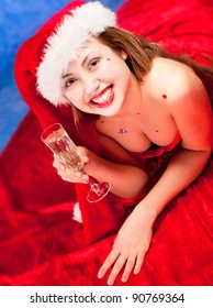Girl wearing santa clothes with champagne glass