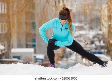Girl wearing sportswear and doing stretching exercises on snow with urban background. Winter sports, outdoor fitness, fashion, workout, health concept.