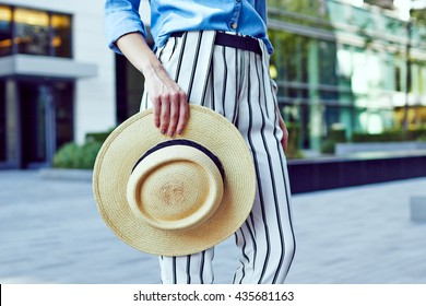 Girl wearing stripe pants holding a straw hat outside the city, urban landscape