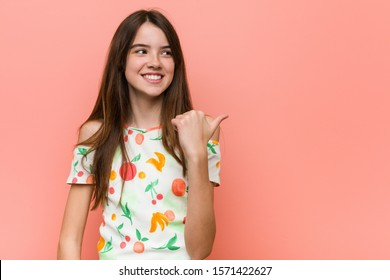 Girl wearing a summer clothes against a red wall points with thumb finger away, laughing and carefree.