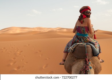 Girl wearing sunglasses, sandals, harem pants and a red turban rides a camel across the thin sand dunes of the in Western Sahara Desert, Morocco, Africa, as she looks back at the expedition.