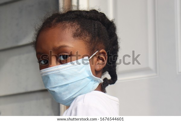 Girl Wearing surgical mask standing on house back porch with white door