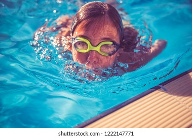 Girl wearing swimming goggles rising from swimming pool