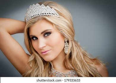 Girl wearing tiara and sparkling jewlery.