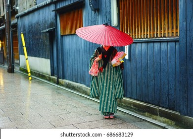 Girl wearing traditional Japanese clothing with umbrella during festival in Kyoto, Japan. Selective focus on a girl.