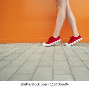 Girl wearing trendy red shoes. Shoes close up shoot in front of orange wall for fashion store, a lot of copyspace. Young woman with sexy legs near color wall