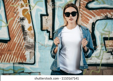 Girl wearing t-shirt and cotton jacket posing against street , urban clothing style. Street photography