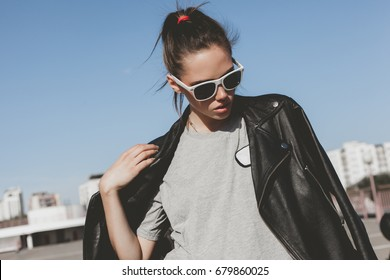 Girl wearing t-shirt and leather jacket posing against street , urban clothing style