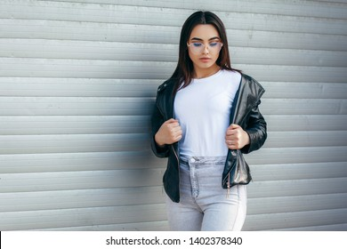 Girl wearing t-shirt with place for logo, glasses and leather jacket posing against street
