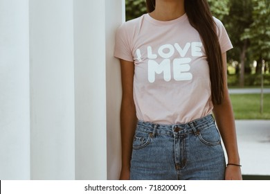 "Girl is wearing t-shirt with a text "" I love me"""