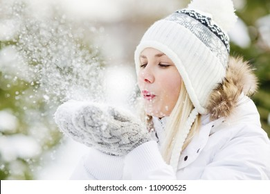 A Girl Wearing Warm Winter Clothes And Hat Blowing Snow In Winter Forest, horizontal