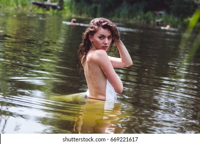 girl wearing a white cloth bathes in the river