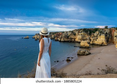 Girl wearing white dress and hat looking out on the ocean. Lagos, Algarve Coast, Portugal
