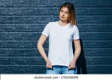 Girl wearing white t-shirt posing against street , urban clothing style. Street photography