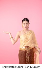 The girl wears an ancient Thai dress on a pink background.