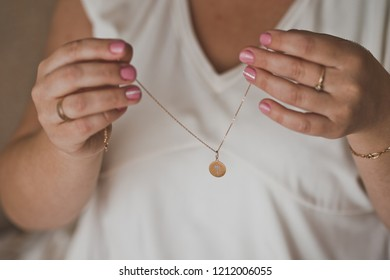 The girl wears a pendant around her neck on a gold chain.