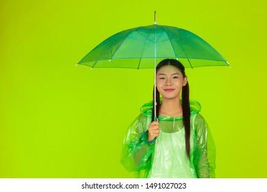 Girl wears a rain green dress and holds a rain umbrella on a green background.