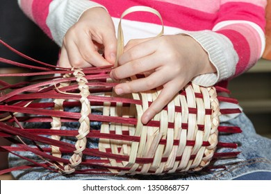 The girl weaves a willow ribbon. Children's hands make wicker crafts. Making a basket in the workshop