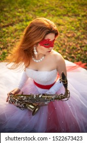 A girl in a wedding dress with a red garter and a red lace mask, in an autumn park, with a saxophone in hands.