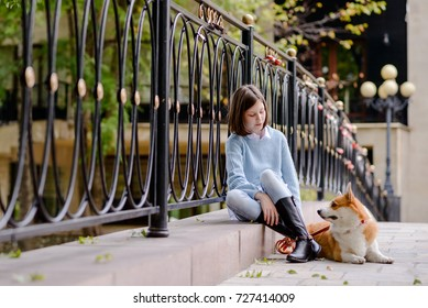 A girl and a welsh corgi pembroke sitting my a bridge fence looking at each other
