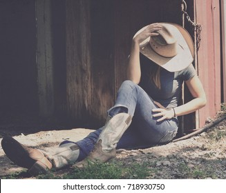Girl in western wear relaxes in shadows of barn, representing agriculture industry in cowboy hat, jeans and cowboy boots.