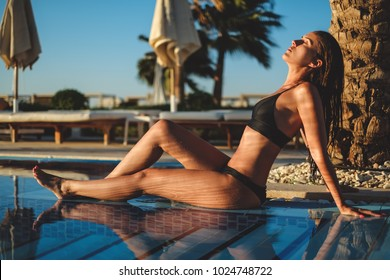 Girl with wet hair and body sitting on the edge of pool enjoying sun