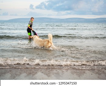 Girl in wet suit in water, holding small surf board, looking and smailing at her dog walking in water. Burren mountains in the background, Galway bay.