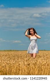 Girl in a wheat field in a blue sky beautiful clouds.