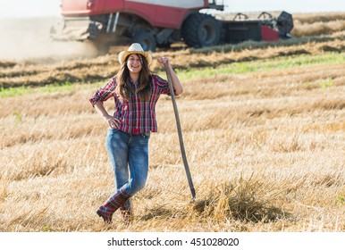 Girl in the wheat field collecting straw