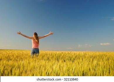 The girl in a wheaten field looks at horizon