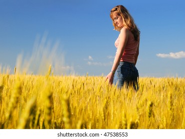 The girl in a wheaten field looks at wheat