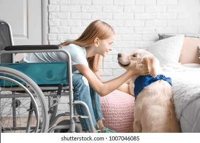 Girl in wheelchair with service dog indoors