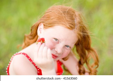 girl which eats a strawberry. Soft focus. Focus on eyes.