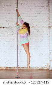 Girl whirls around the pole while performing dance or yoga in the studio with white brick walls