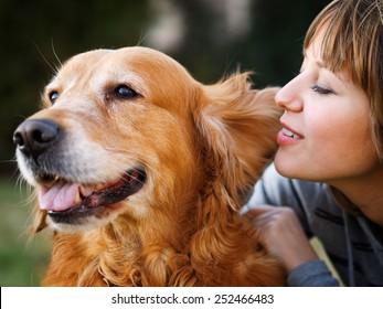 Girl whispering in her dog's ear in the park