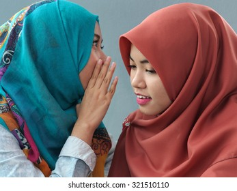 A girl whispering to her friend.