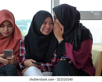 A girl whispering to a smiling friend while another is left out.