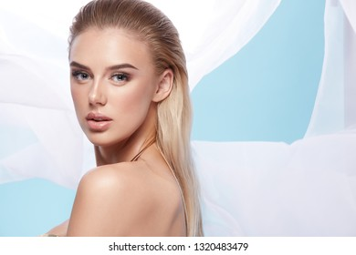 Girl at white background wearing dress and nude make up, portrait. Girl with wet hair and blue eyes. Make up model at white background.